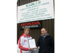 Ben Kelly receiving his Sadler Junior Championship award from Bobby Sadler at the Company's headquarters in Douglas.