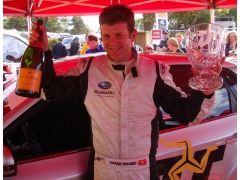 Mark Higgins lifts the champagne after the record breaking lap